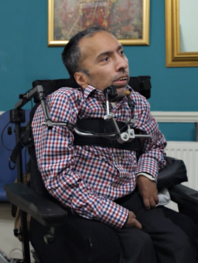 A man in a powerchair in his home