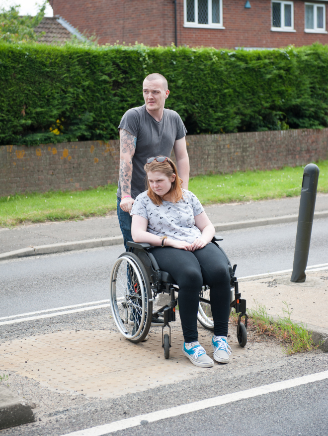 A man pushing a woman in wheelchair across a road