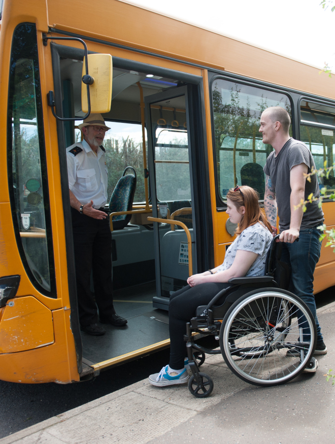 A man pushes a woman in a wheelchair toward the entrance toward a bus where the driver stands in the doorway