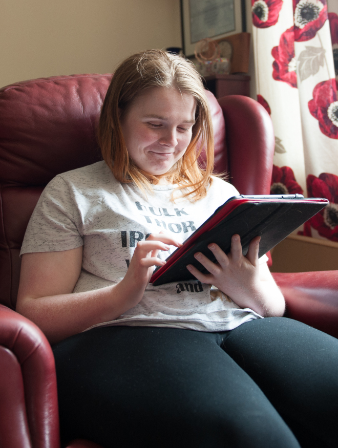 A smiling young woman sitting in a chair looking at a computer tablet device in her living room