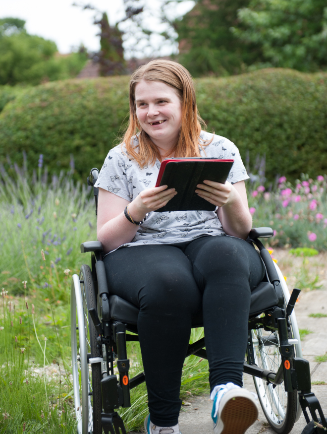A smiling young woman outside in the garden in her wheelchair holding a computer tablet device