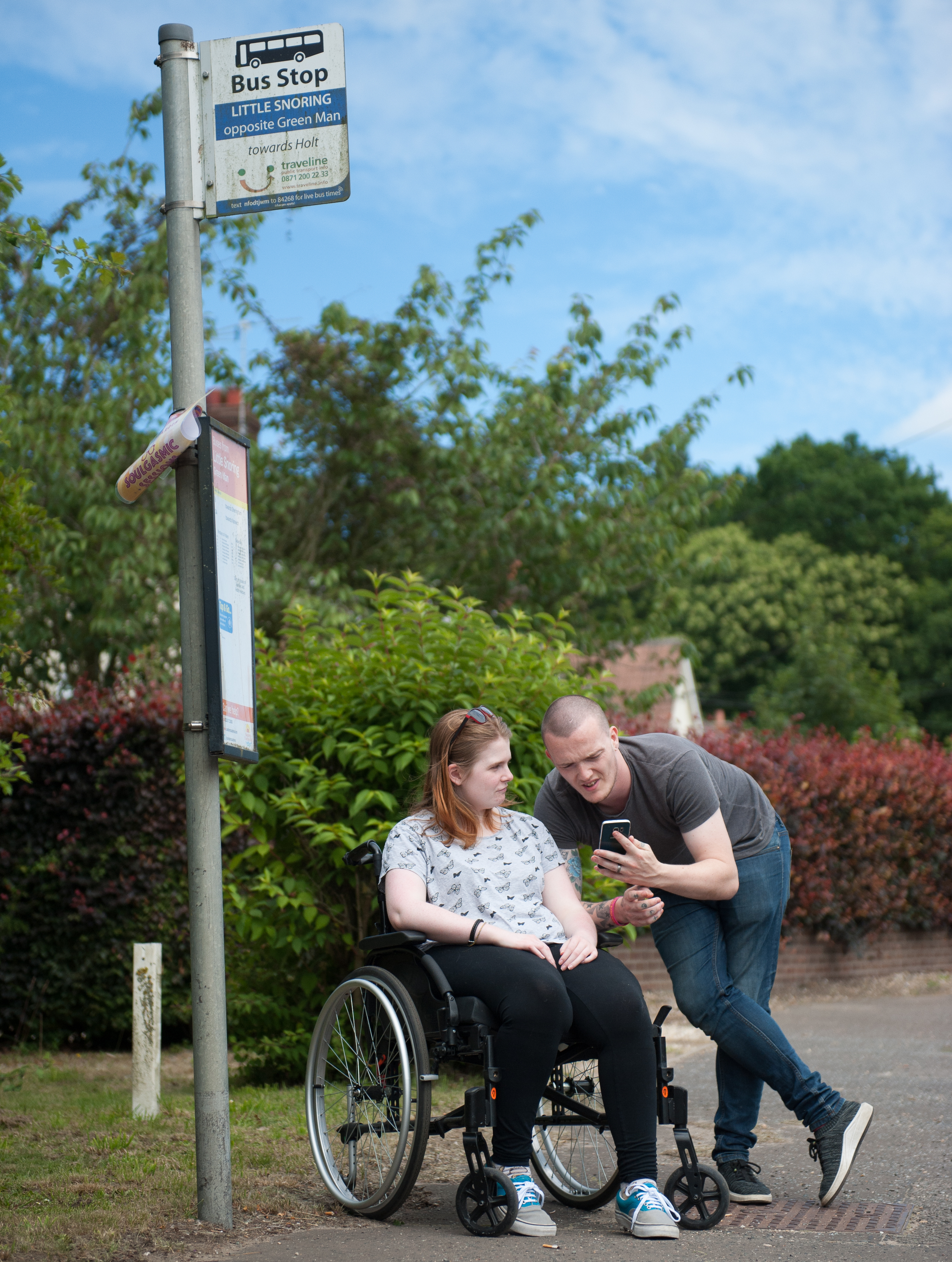 A man shows his phone screen to a woman in a wheelchair as they wait at a bus stop in a rural town