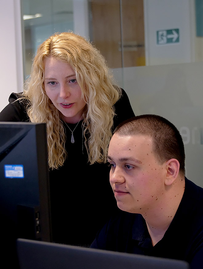 A woman and man looking at a computer screen in an office