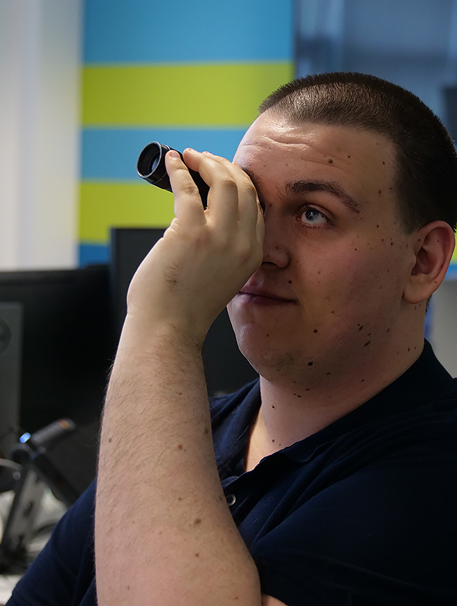 A young man using a monocular viewfinder in an office