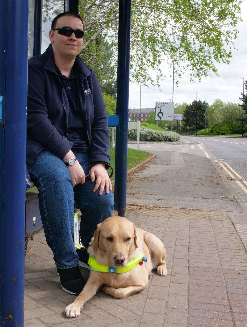 A young man with his guide dog at a bus stop