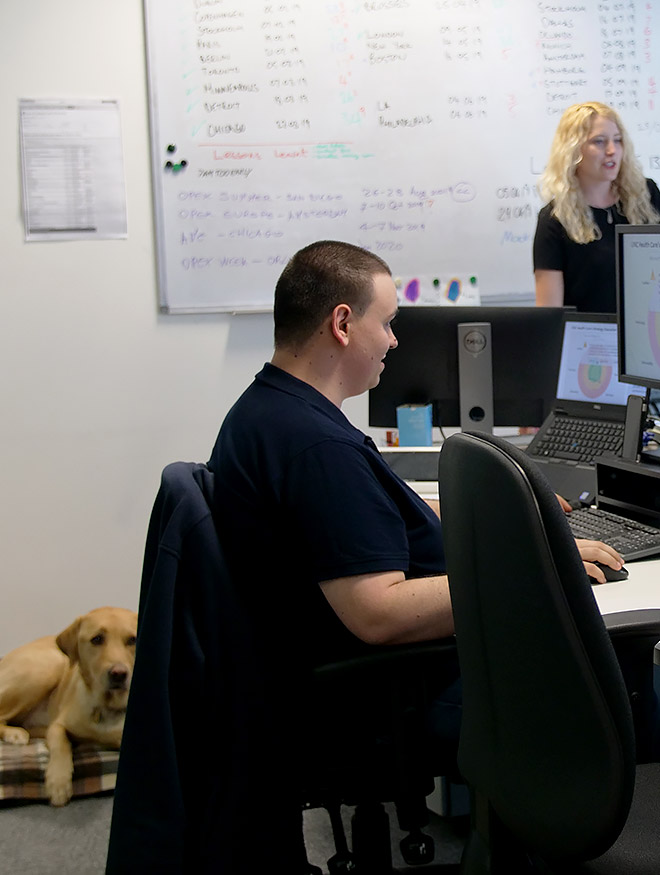 A man sat at a computer in an office. A dog sits on the floor next to him