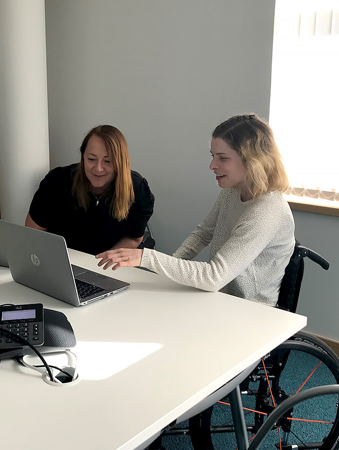 A smiling young woman in a wheelchair with a smiling woman, sitting at a table in an office meeting room looking at a laptop