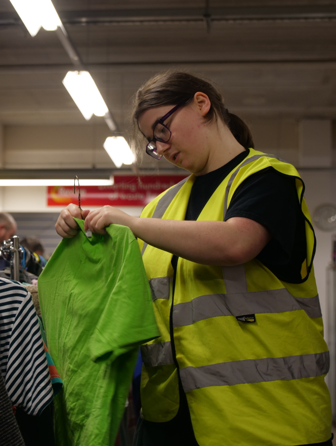 A young woman in a high visibility jacket hanging clothes up in a charity shop