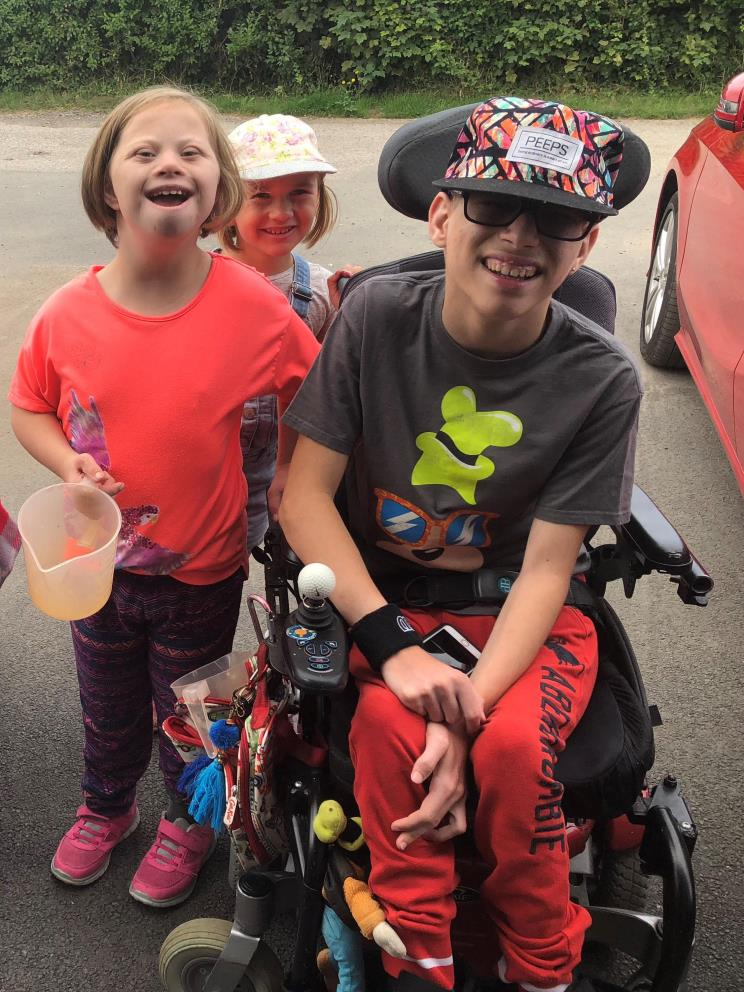 Two smiling girls and one smiling boy in a power chair outside