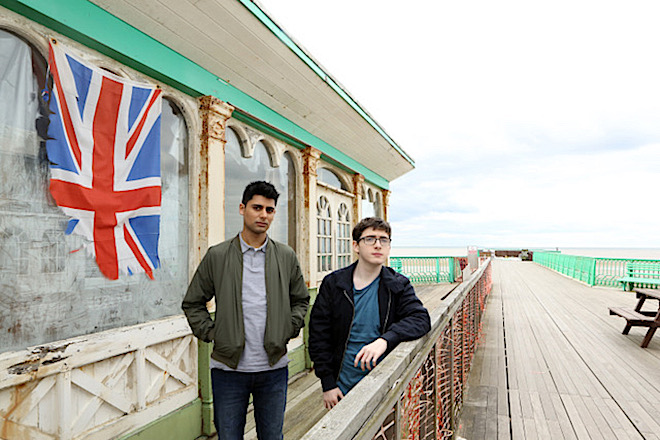 Two young men standing together on a pier