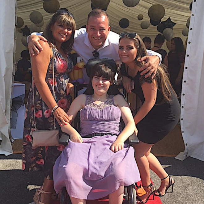 A smiling young woman in a wheelchair with her mum, dad and big sister outside on a sunny day