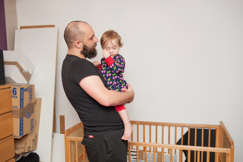 A man holds his 18 month old daughter who looks very tired