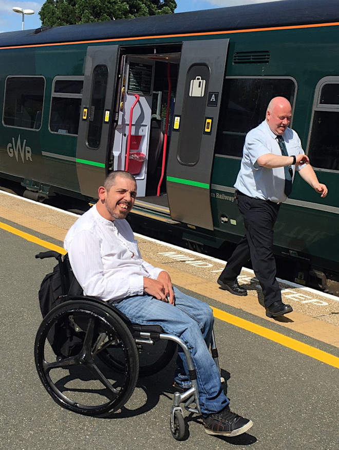 A man in a wheelchair on a train platform