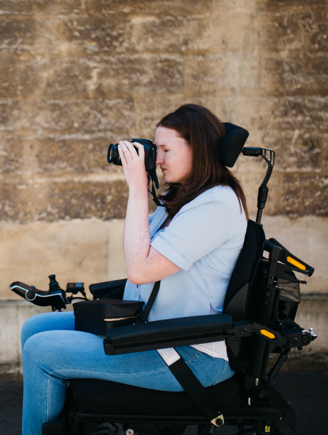 A young woman in a powerchair taking a photograph on the street