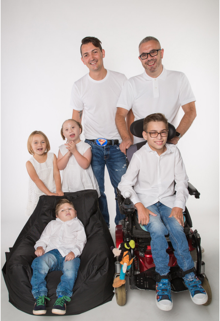 A family photo of the Ratcliffe family - dads Garry and Kyle and their four children, three of whom have impairments.